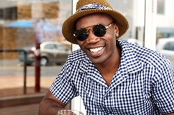 Photo of an African-American man wearing a hat and sunglasses