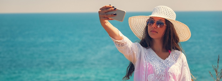 Photo of a woman on a beach wearing a hat and sunglasses taking a photo of herself