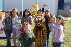 Photo of children gathered around a sunscreen dispenser provided by Nevada's Sun Smart Schools program