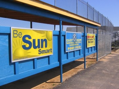 Photo of a shade structure for a school athletic field. Signs on the structure say Be Sun Smart, East Meadow Association Pony Field, and Stop Melanoma Skin Cancer.