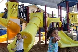 Photo of children playing under a shade structure funded by the American Academy of Dermatology