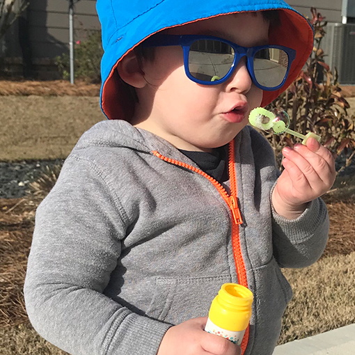 Child wearing sun protection gear and blowing bubbles.