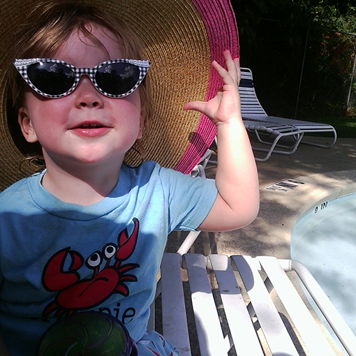 Girl showing off her sun-safe style at the pool with a wide-brimmed hat and sunglasses.
