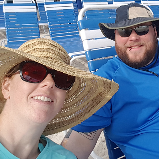 MaryBeth and Brandon wearing wide-brimmed hats and rash guards at the beach.