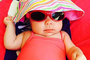 Photo of a baby girl with sunglasses.