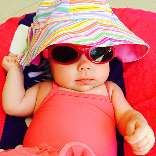 Baby keeping it cool with a wide-brimmed hat and shades.
