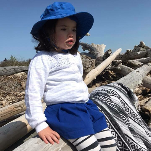 Girl staying sun safe while enjoying time at the beach in Hansville, Washington.