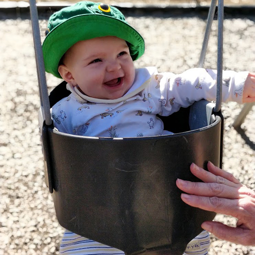 Baby staying sun-safe in a swing.