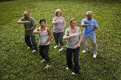 Photo of a group of men and women participating in a tai chi class