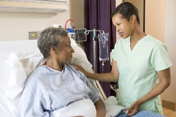 Photo of a nurse talking to a woman in a hospital