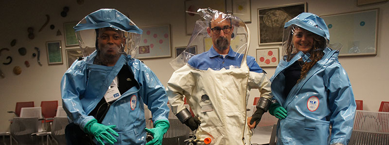 Fellows try on biosafety suits during a tour of the David J. Sencer CDC Museum
