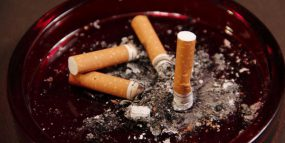 Image of an ashtray, containing four used cigarette butts and ashes