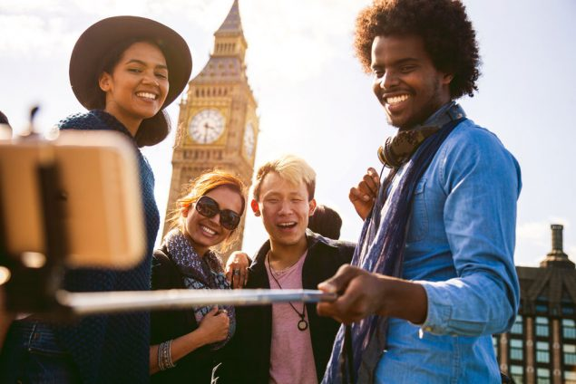 Group of four friends taking a selfie with a selfie stick while traveling overseas