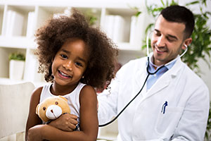 Smiling girl examined by doctor