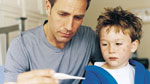 Father Checking Temperature of Son Sick With Chickenpox.