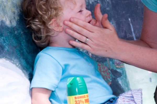 A mother applying insect repellant to a toddler's face with her hands.
