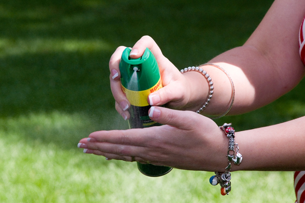 Person spraying bug repellant on the hand.