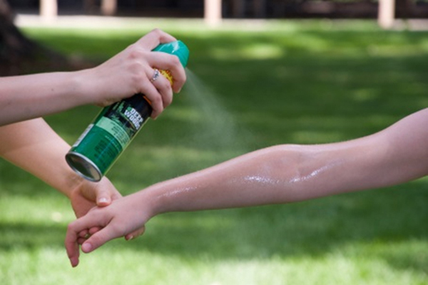 Person applying insect repellant on another person's arm
