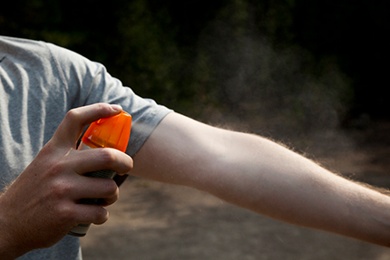 A man is spraying bug spray on his arm.