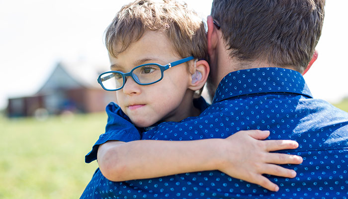 A boy with a hearing aid, hugging his father.