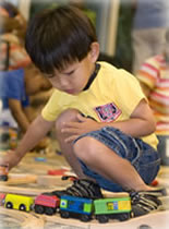 Photo of little boy playing with toy train.