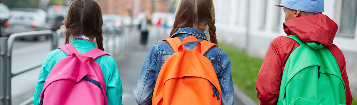 Three kids with colorful backpacks going to school