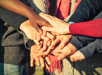 Photo of many people with their hands in the middle of a circle together.