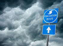 Photo of hurricane evacuation sign with storm in the background.