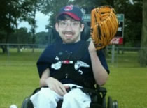 Zac posing in his wheel chair for his baseball team photo