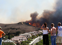 Photo of people looking at a wildfire.