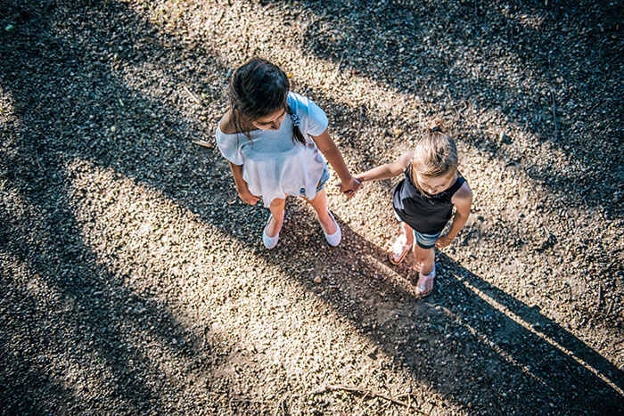 Two girls holding hands on playground