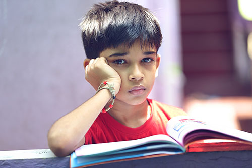 Young boy looking up from a book with a sad face
