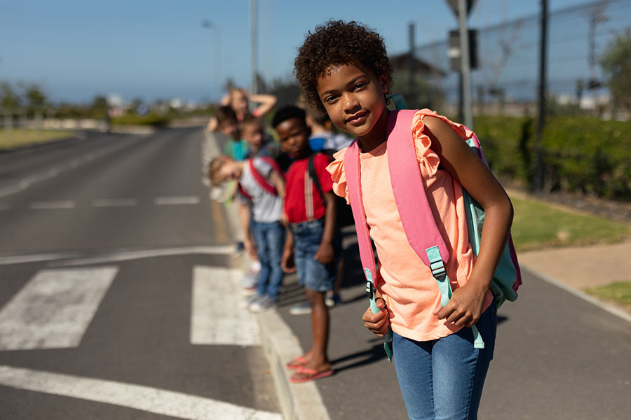 Schoolchildren looking for traffic while waiting to cross the road
