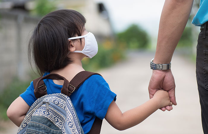 Little girl with backpack wearing cloth face mask hand in her father's hand waiting for school bus. Children need help with the transition back to school.