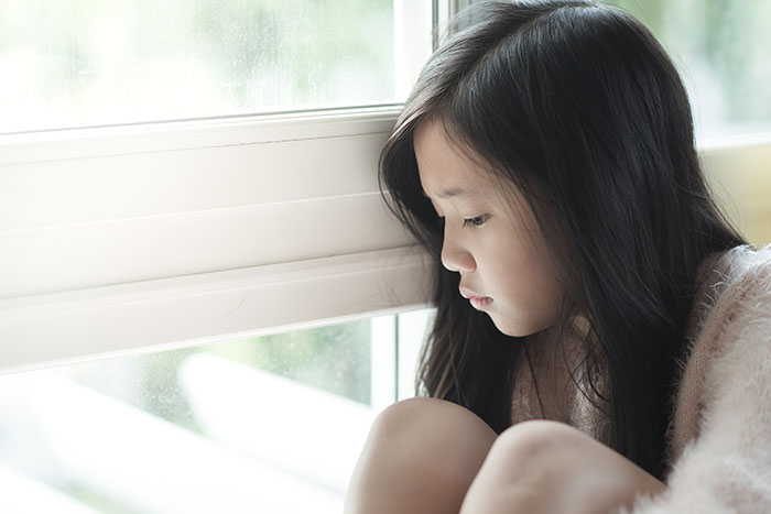 Portrait of sad Asian girl sitting in a window sill