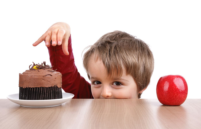 A young boy choosing between a cake or an apple