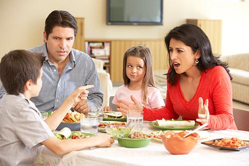 Family sitting at dinner table arguing..