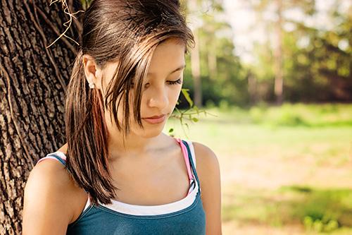 Adolescente que se inclina contra un árbol