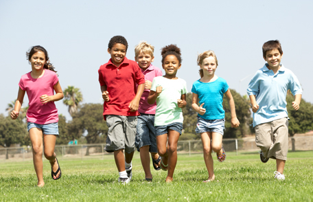 Photo of a group of school-age children running outside