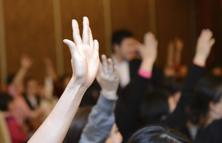 Photo of hands being raised at a meeting