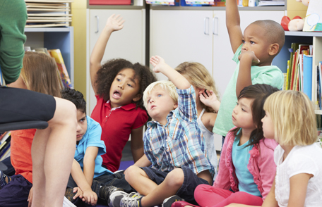 Photo of a group of preschoolers raising their hands in a classroom