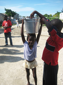 A girl carrying a pail of water.