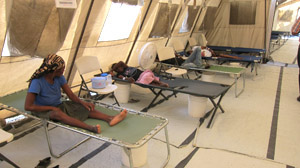 People laying down on cots in a makeshift treatment facility in Haiti.