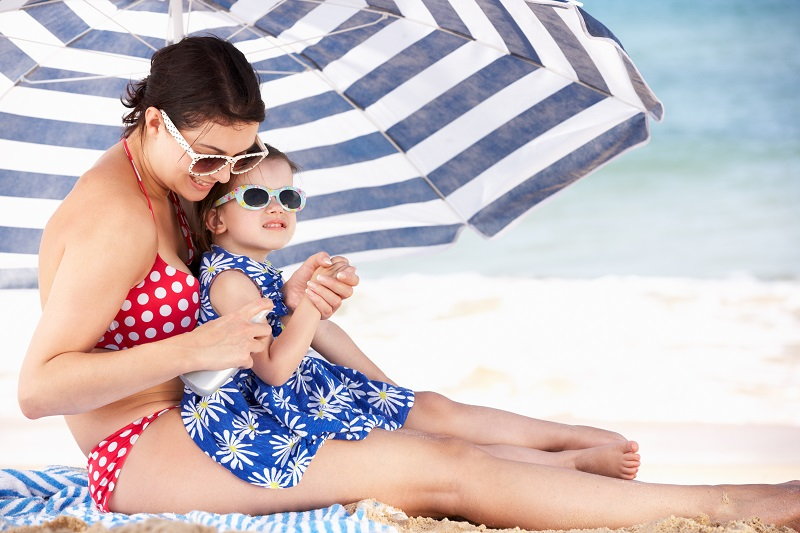 mother and child sitting under umbrella on beach