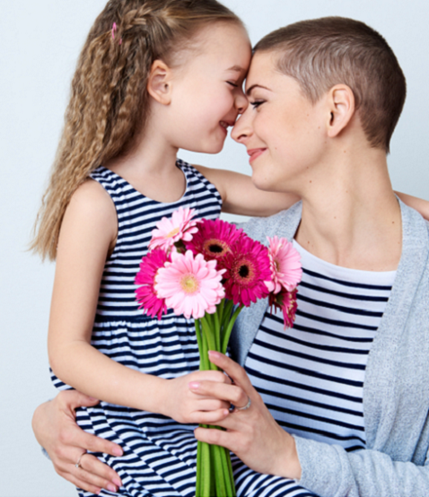 image of a cancer patient with a child in her lap, holding flowers and smiling