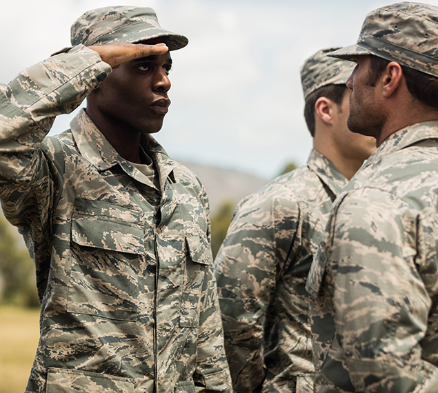 Photo of men in the military. One of them saluting to his superior.