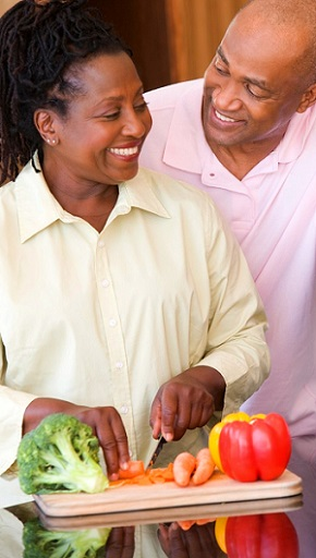 man and woman cutting fresh vegetables