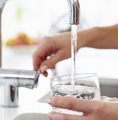 A woman pouring herself a glass of water from faucet.