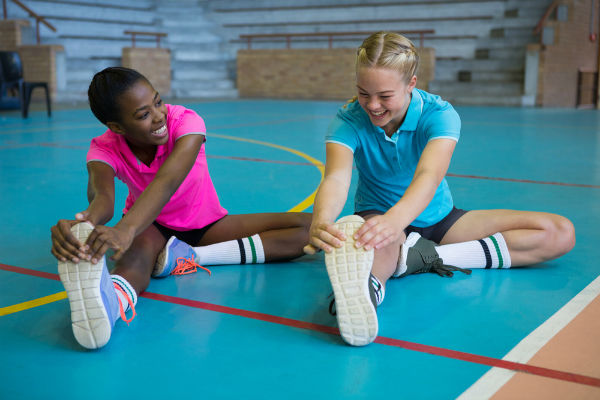 teenage girls stretching before exercising in a gym
