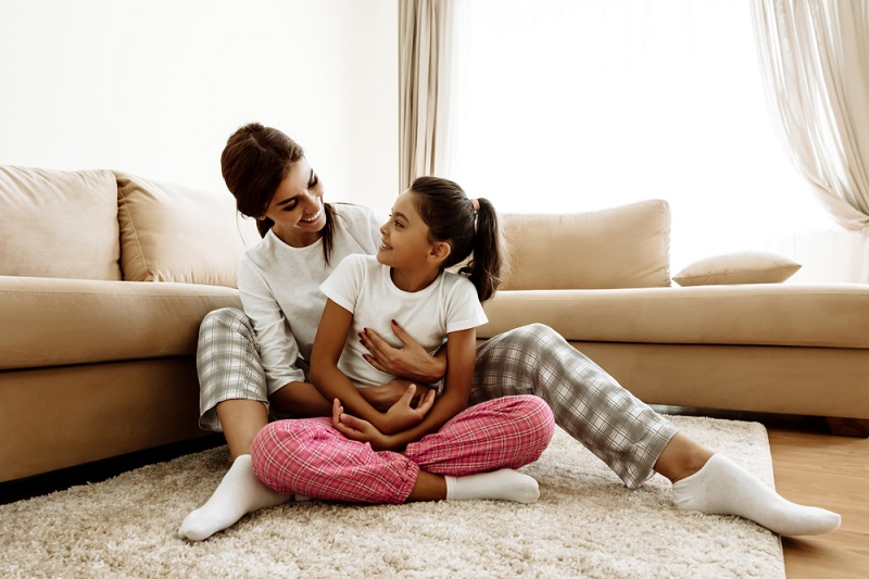 mother with arms around daughter sitting together on carpet
